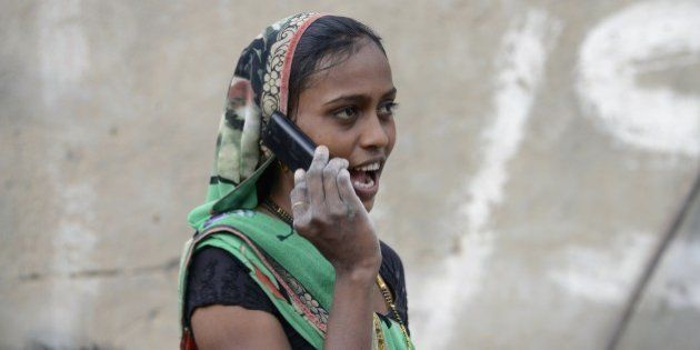 An Indian woman speaks on a mobile phone in Suraj village in Mehsana district, some 100 km from Ahmedabad,...