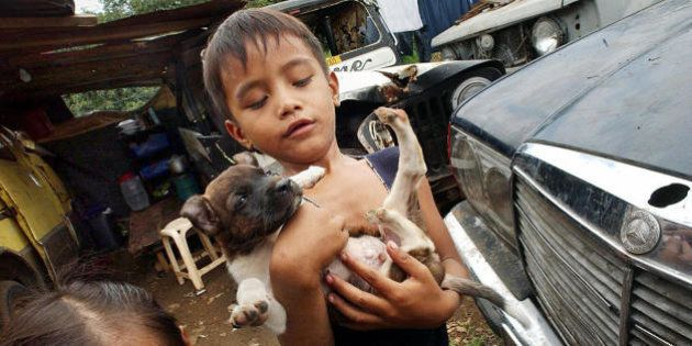 Two Filipino squatter children Jumel Alonte and her younger sister Angel (L) play with their puppy in...