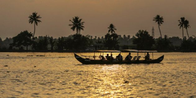 Tourists travel in a boat along the backwaters at sunset in Alappuzha, Kerala, India, on Saturday, May...
