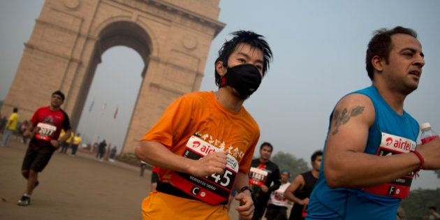A participant wears a mask as he runs past the India Gate memorial during Delhi Half Marathon in New...