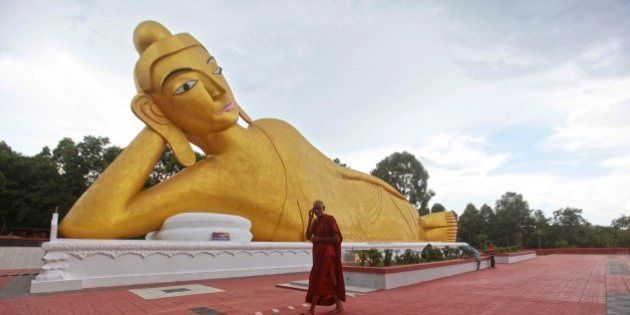 A Bangladeshi Buddhist monk walks in front of a Buddha statue at one of the rebuilt Buddhist temples...