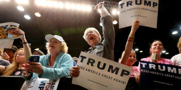 Donald Trump supporters listen to U.S. Republican presidential candidate Donald Trump speak at a campaign...
