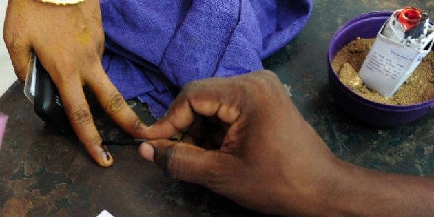 An Indian electoral official marks the finger of a voter with ink at a polling station in Chennai on...