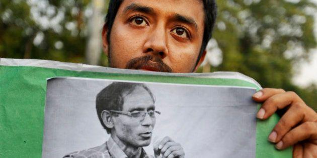 A Bangladeshi student holds a portrait of a University Professor A.F.M. Rezaul Karim Siddique during...