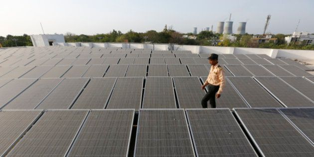 An Indian security man walks amid rooftop solar plant at the secretariat gymkhana in Gandhinagar, India,...