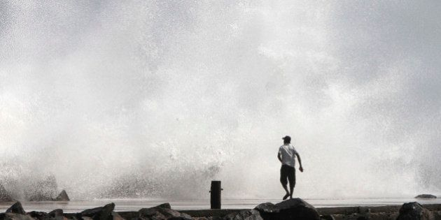 A man watches a large wave during high tide at a fishing harbour in Chennai December 28, 2011. The coastal...