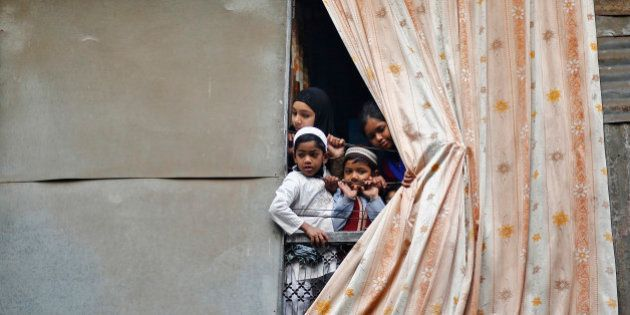 Muslim children peep through an opening of their house to watch a religious procession to mark Eid-e-Milad-ul-Nabi,...