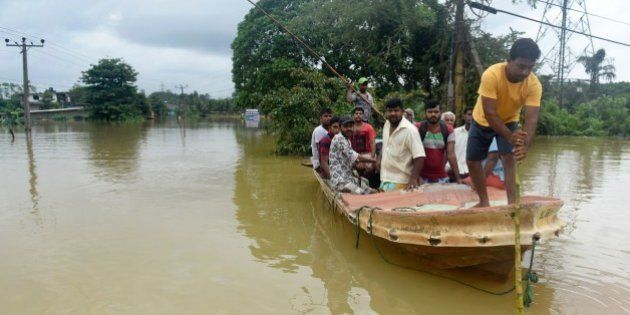 Sri Lankan residents travel by boat through the floodwaters in Pugoda, about 35 kms from capital Colombo...