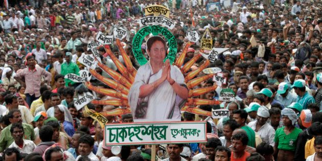 Indian West Bengal state's Trinamool Congress party (TMC) supporters carry a cutout of their leader...