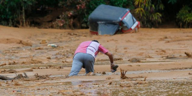 An onlooker struggles to get out after getting stuck in the mud after a landslide in Elangipitiya village...
