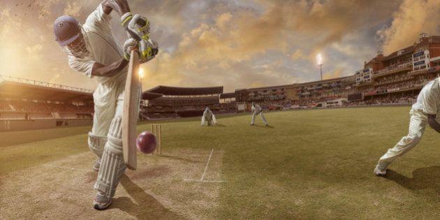 Batsman just after hitting ball in professional cricket match in full stadium at sunset during summer.Stadium...