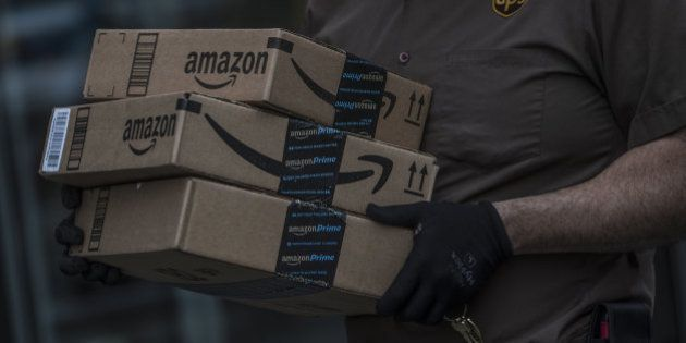 A United Parcel Service Inc. (UPS) delivery driver carrries Amazon.com Inc. packages near the Fulton...