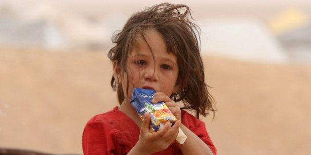 A Syrian refugee child drinks as families wait to enter Jordanian side of the Hadalat border crossing,...