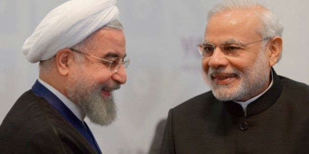 Iran's President Hassan Rouhani, left, smiles as Indian Prime Minister Narendra Modi speaks to him during...