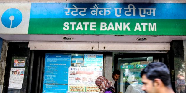 People stand outside a State Bank of India building that houses automated teller machines (ATM) in Nagpur,...
