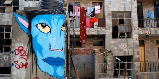 A woman looks out from the balcony of her house, as a street-art resembling a character from the Hollywood...