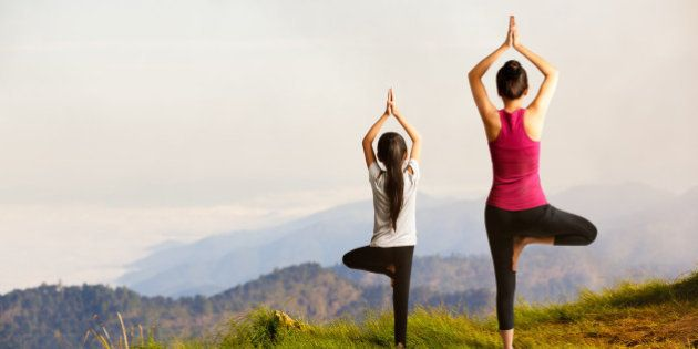 Mother and daughter doing yoga at top of
