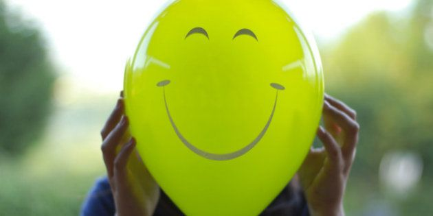 Portrait of a woman in a garden holding a green balloon in front of her face, with a happy face painted...
