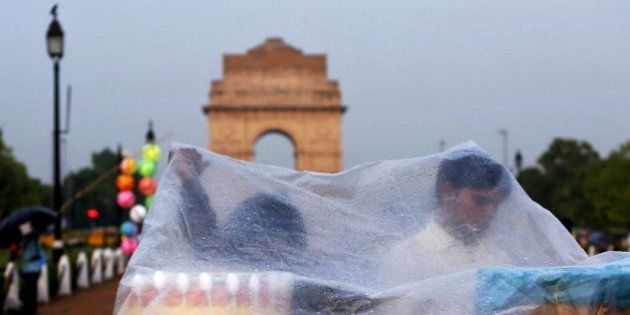 Roadside eatery hawkers use a plastic sheet to cover themselves from a rain shower in front of India...