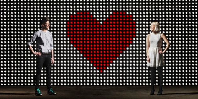 young couple in front of light wall, with huge heart made of red dots,