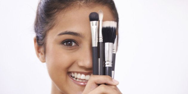 A young woman holding makeup brushes against her
