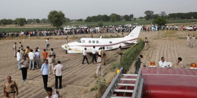 Security personnel secure the site where an air-ambulance, carrying seven passengers, crash landed after...