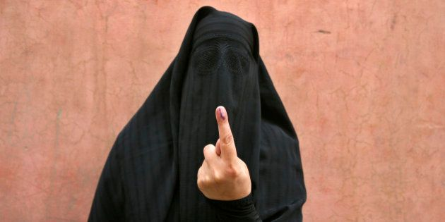 A veiled Muslim woman shows her ink-marked finger after voting outside a polling station in Doda district,...