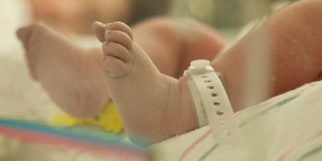 Close up on the tiny feet of a newborn baby girl, laying in a hospital bed as her mother rests in the
