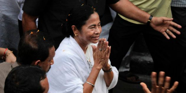 Trinamul Congress leader Mamata Banerjee greets people with folded hands as she walks in a road show...
