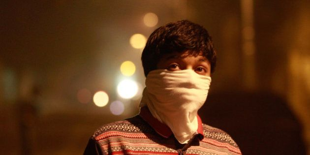 NEW DELHI, INDIA - NOVEMBER 11: A child takes precautions against air pollution as fire crackers add...