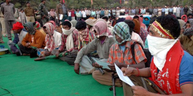 Naxalites with their faces covered sit as they await to surrender before the Chief Minister of Chhatisgarh...