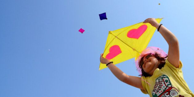 Little girl try to flying kite,