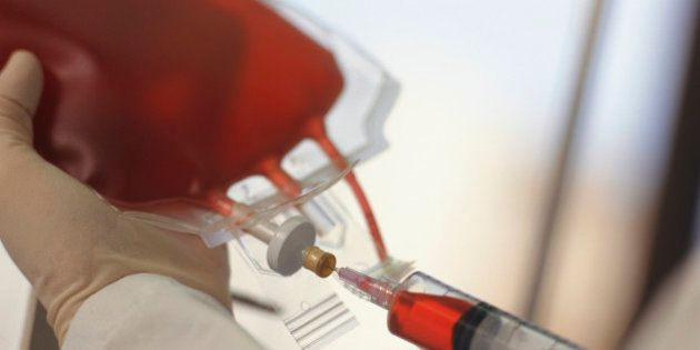 Technician drawing blood with syringe from blood bag, Close-up of