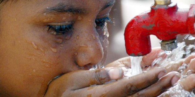 A street child drinks water from a tap in a slum area of New Delhi June 4,2003 to quench his thirst during...