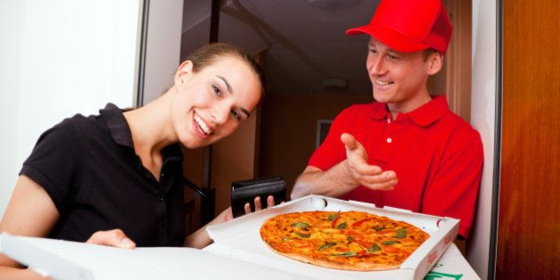 delivery boy presenting a hot pizza to a female customer at her