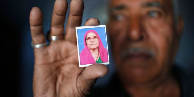Kasam Bhai Mansoori, a Muslim, displays a photograph of his mother Sona Ben Mansoori at his house which...