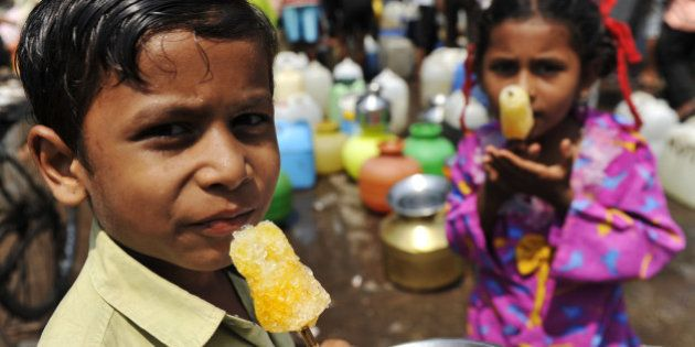 Indian children enjoy ice lollies as they wait for their mothers to fill containers with drinking water...