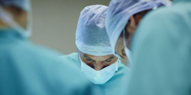 Male surgeons working in operating room at