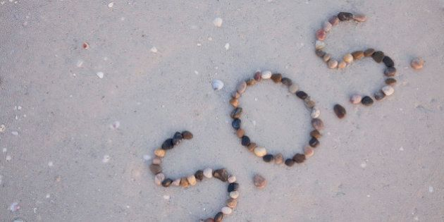S.O.S written on the beach with