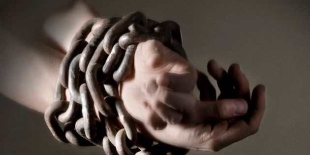 Close-up of wrists and hands bound in heavy metal