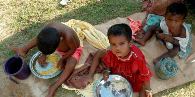 Homeless children eat food at a slum area on the outskirts of Agartala, capital of India's northeastern...