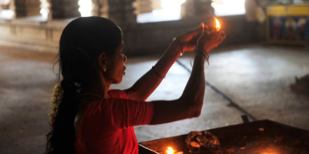 Woman holding candle inside Hindu Sri Srirangam Temple in Trichy (Tiruchirapalli) in Tamil Nadu,South...