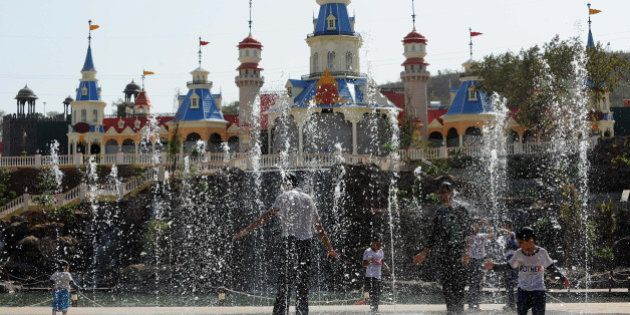Indian visitors play inside a water fountain at the Adlabs Imagica theme park at Sangewadi some 100 kms...