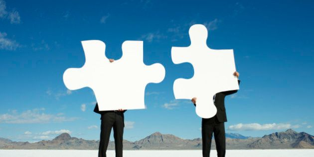 Businessmen Joining Giant Puzzle Pieces in