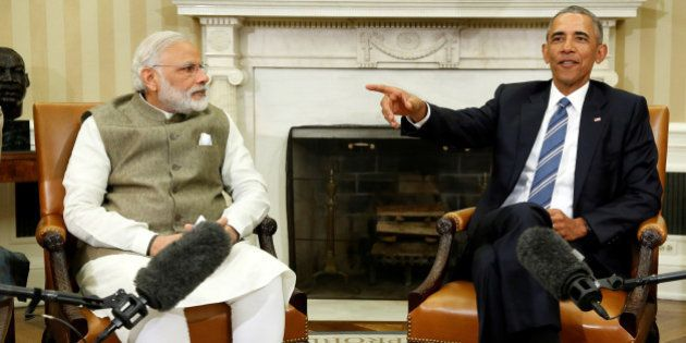 U.S. President Barack Obama (R) encourages reporters to spread out and fill the room as he and India's...