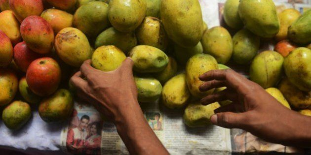 An Indian shopkeeper arranges mangoes for sale during the 4th Gitanjali Mango Festival in Siliguri on...