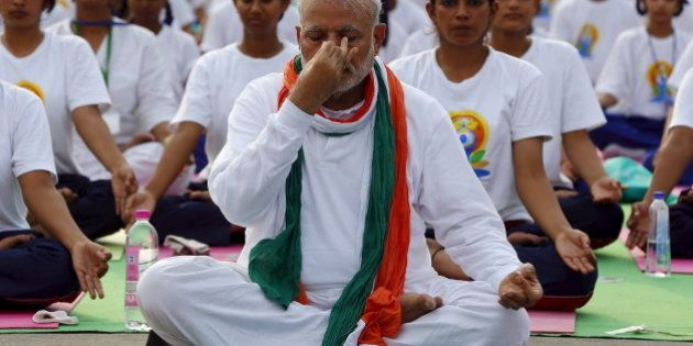 India's Prime Minister Narendra Modi performs yoga with others to mark the International Day of Yoga,...
