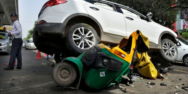 GURGAON, INDIA - JULY 15: People looking at the Hyundai SUV car which crashed into an auto-rickshaw after...