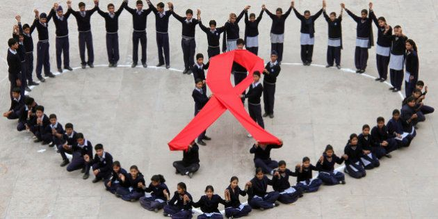 Students make a formation in the shape of a heart and a red ribbon during a HIV/AIDS awareness campaign...