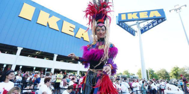 A stilt-walker dances as people wait for IKEA, the world's leading home furnishings retailer. to open...